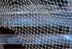 在蓝色,灰色木背景的捕鱼网 库存图片
