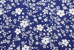 在蓝色织品样式背景的花 免版税库存照片