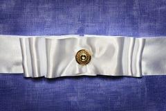 在蓝色织品背景的白色丝绸弓 免版税图库摄影