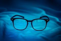 在蓝色织品背景的读书镜片 免版税图库摄影