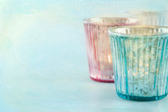 在蓝色织地不很细背景的淡色蜡烛 免版税库存照片