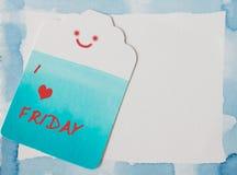 在蓝色水彩框架和商标纸的愉快的星期五 库存照片