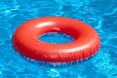 在蓝色水池的可膨胀的红色游泳圆环 库存照片