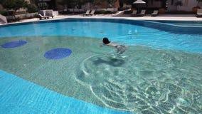在蓝色水池水的年轻美好的妇女游泳 股票视频