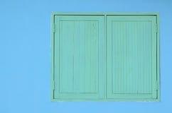 在蓝色水泥墙壁上的绿色木窗口 免版税库存图片
