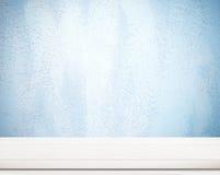 在蓝色水泥墙壁的空的白色木桌 库存照片