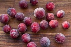 在蓝色玻璃和木背景的冷冻莓果 库存照片