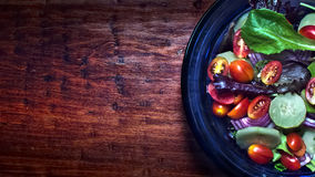 在蓝色玻璃碗的新鲜的沙拉在木桌面 免版税库存图片