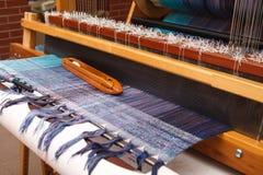 在蓝色经线的编织的梭在织机 免版税库存照片