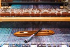 在蓝色经线的编织的梭在织机 库存图片