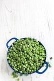 在蓝色滤锅的冷冻豌豆 库存照片