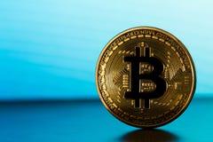 在蓝色backround的一bitcoin 图库摄影
