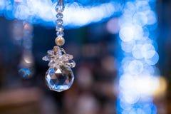 在蓝色bokeh球backgr隔绝的水晶圣诞节装饰 免版税库存照片