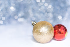 在蓝色bokeh背景的金黄和红色圣诞节球 库存图片