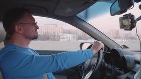 在蓝色longsleeve的白色司机集中于驾驶在城市道路 股票录像