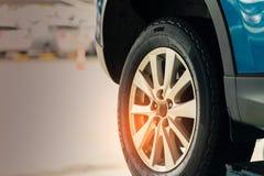 在蓝色SUV汽车后轮的选择聚焦在被弄脏的背景 有新的高性能轮胎的汽车在车库车间停放了 库存照片