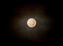 在蓬松云彩后的满月在晚上 免版税库存照片