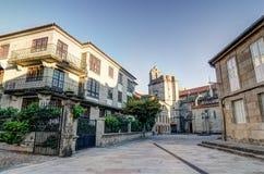 在蓬特韦德拉西班牙有一个教会的作为背景和一些大厦的一个正方形与植物和西班牙旗子 免版税图库摄影