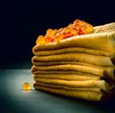 在薄煎饼堆的红色鱼子酱在黑色 免版税库存照片
