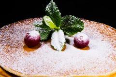 在薄煎饼的红色蔓越桔莓果用绿色薄菏洒与在黑背景的搽粉的糖 库存照片