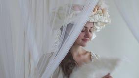 在薄纱挥动的羽毛爱好者附近的年轻美丽的兴高采烈的妇女调情的人在白色背景 女孩佩带白色礼服和白色 影视素材
