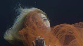 在薄绸的礼服的妇女美人鱼游泳在水面下在黑暗的背景的 股票视频
