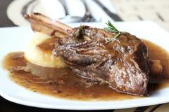 在薄菏和迷迭香小汤的被炖的羊羔小腿 免版税库存图片