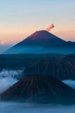 在薄雾和抽烟的火山Bromo的山 免版税库存图片