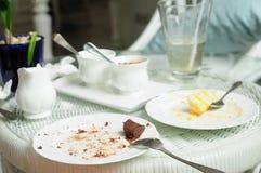 在藤条桌上的被弄脏的蛋糕板材 免版税库存照片