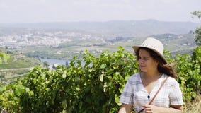 在藤植物之间的领域的年轻女人用葡萄 影视素材