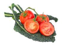 在藤的蕃茄坐绿色无头甘蓝离开 免版税图库摄影