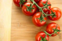在藤的西红柿反对木切板 库存照片
