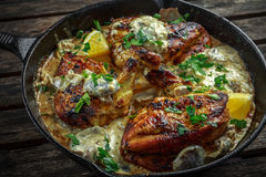 在蘑菇酱油的乳脂状的鸡fellets supremes用在土气生铁长柄浅锅的荷兰芹 库存照片
