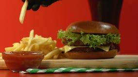 在蘸在番茄酱,便当餐馆,关闭的手套的手薯条  股票录像