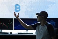 在虚拟现实世界的人控制Bitcoin 免版税图库摄影