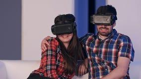 在虚拟现实耳机观看的电影的微笑的夫妇 免版税库存照片