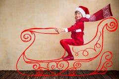 在虚构的圣诞老人雪橇的儿童驱动 免版税图库摄影