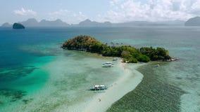 在蛇岛、沙洲和盐水湖附近的盘旋的空中英尺长度有绿松石天蓝色的浅水区的 El nido? Palawan 股票录像