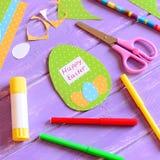 在蛋形状的愉快的复活节卡片 创造复活节纸贺卡的材料和工具 孩子的容易和乐趣复活节纸工艺 库存照片