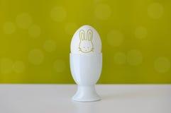 在蛋杯的一个鸡蛋在绿色背景 免版税库存照片