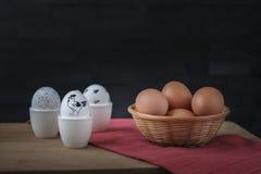 在蛋杯的白色复活节彩蛋和在篮子的红皮蛋 免版税库存照片