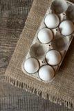 在蛋盒的未加工的鸡蛋在木背景 免版税库存图片