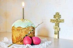 在蛋糕和十字架的基督徒复活节静物画灼烧的蜡烛 免版税库存图片