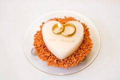 在蛋糕的婚戒 免版税库存图片