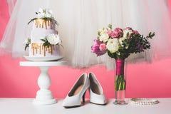 在蛋糕立场的婚宴喜饼与白色礼服和花束 库存照片
