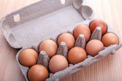 在蛋纸盒的红皮蛋在厨房用桌上 免版税库存照片