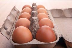 在蛋纸盒的红皮蛋在厨房用桌上 库存图片