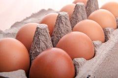 在蛋纸盒的红皮蛋在厨房用桌上 库存照片