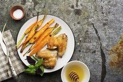 在蜂蜜釉的被烘烤的红萝卜用大蒜、橄榄油、贤哲和大蒜与鸡翼午餐的与蓬蒿叶子  库存图片
