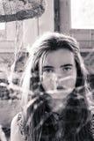 在蜘蛛网后的十几岁的女孩 库存照片